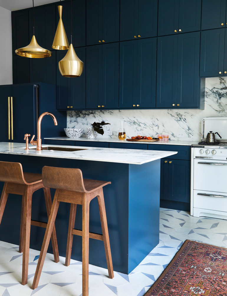 blue kitchen cabinets mixed with brass gold and metallic accent design pieces