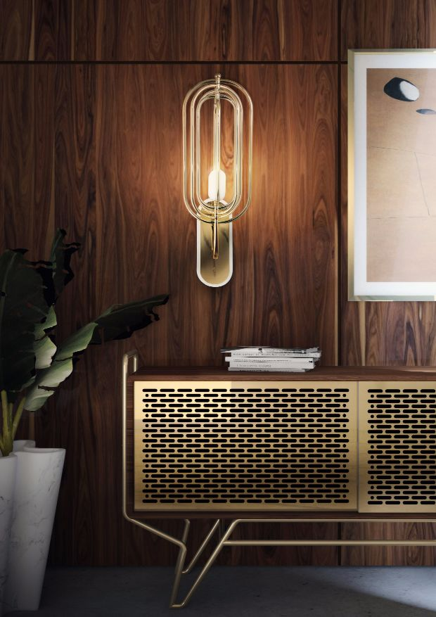 Brass lamp and gold furniture piece mixed with natural looking wood wall pieces