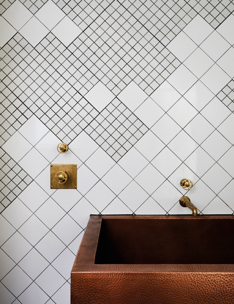 unique textured tile with varying mixed shapes on a wall next to a copper basin with gold handles