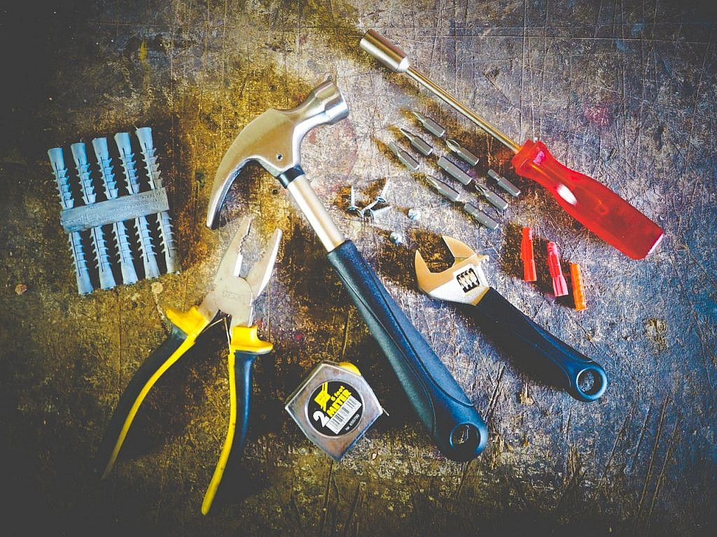 A toolkit comprising nails, pliers, a tape measure, a hammer, a wrench, and a screwdriver.